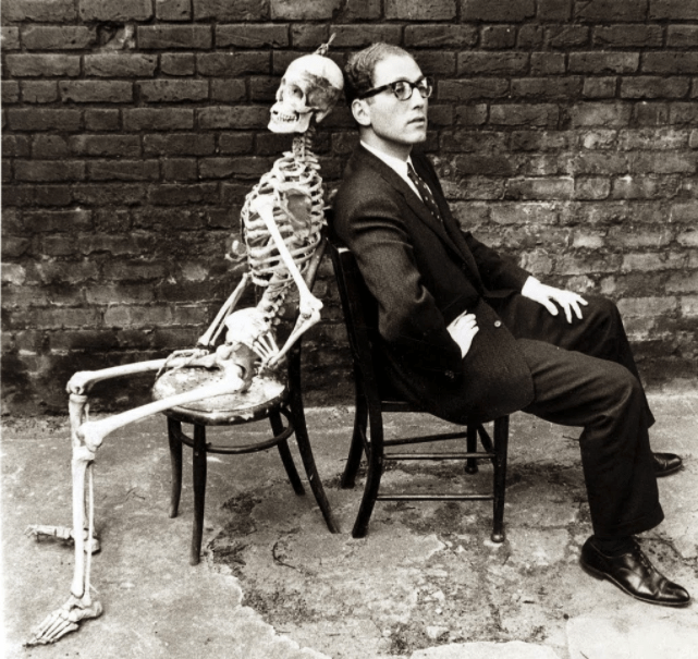 Black and white photo of Tom Lehrer sitting in a chair, back-to-back with an anatomical skeleton.