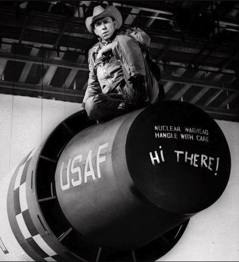Black and white image of actor Slim Pickens as Major Kong sitting atop a prop version of a USAF nuclear warhead. Painted on the warhead are the words Nuclear Warhead Handle With Care. Below that, someone else has painted the words Hi There!