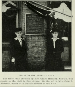 Black & White photo from a May, 1917 newspaper showing two sour-faced old white women in dark dresses and large hats standing on either side of the Pulaski, Tennessee plaque advertising the lie that the Ku Klux Klan was founded on December 24th, 1856.