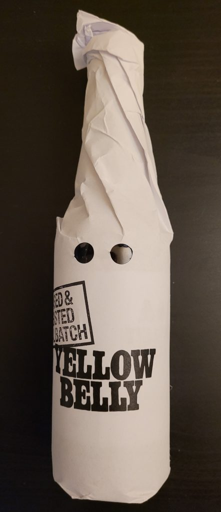 Image of a bottle of Yellow Belly Imperial Stout - Ceased & Desisted Batch. Letters are printed in black on bright white paper wrapped around the bottle. Two parallel holes have been punched in the paper to indicate eye holes. The overall effect is to make the wrapping look like a hood worn by a Ku Klux Klansman.