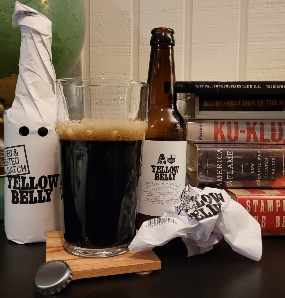 Image of two bottles of Yellow Belly Imperial Stout -- the one on the left remains in its white paper wrapper, the one on the right is unwrapped and opened. Between the two bottles is a beer glass three-fourths full with a nearly-black beer that has a dark tan head. Behind the opened bottle on the right is a stack of books referenced in this episode.