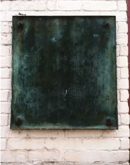 Image of the 1917 KKK bronze plaque gone green with age. The plaque has been turned to the wall and reattached so that the information about the KKK is no longer visible.