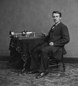 Image of Thomas Edison at an early version of the phonograph