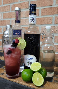 Photo of ingredients for making a Bramble cocktail: Gin, blackberry liqueur, simple syrup, fresh limes.