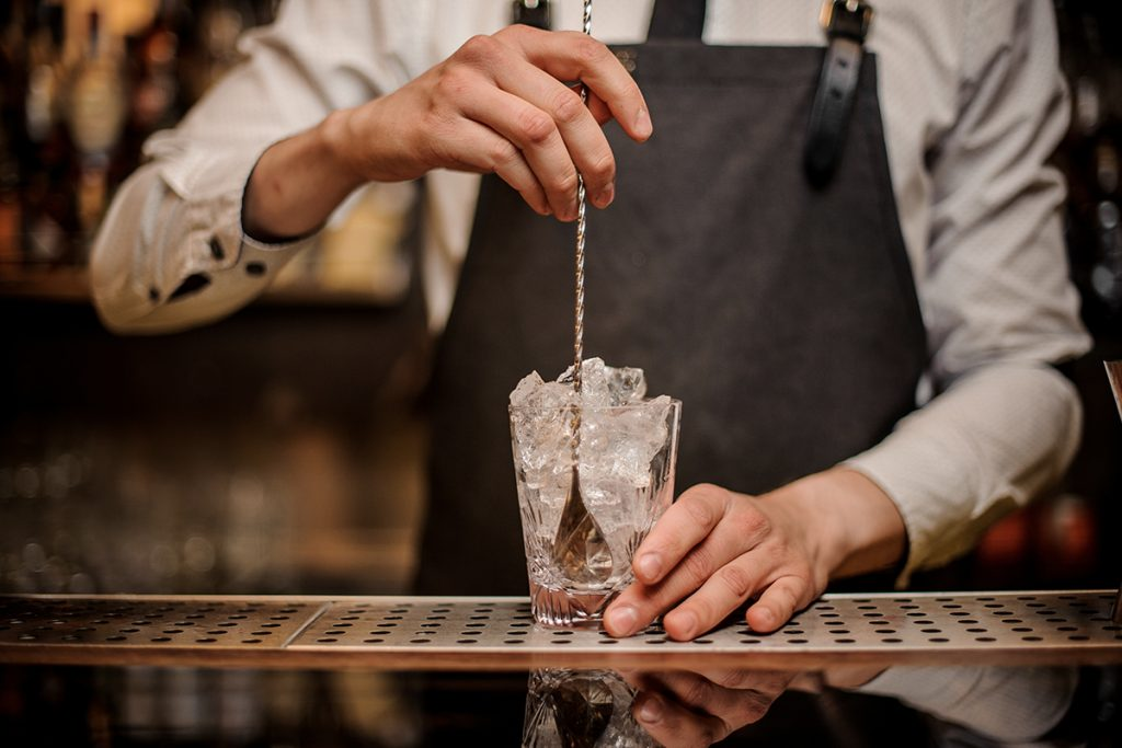 Photo of a bartender's hands holding a glass full of ice cubes in one hand and a cocktail spoon in the other and is read to stir.